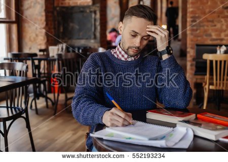stock-photo-portrait-of-man-sitting-at-the-table-with-a-books-in-a-cafe-thinking-man-writing-on-paper-people-552193234